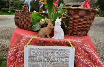 Easter baskets on table with red tablecloth, sign hanging from table stating
