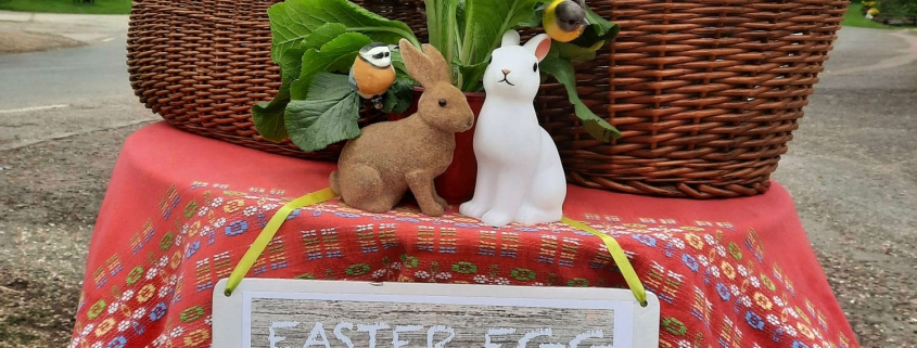 """Easter baskets on table with red tablecloth, sign hanging from table stating """"easter egg hunt"""", 2 easter bunny ornaments on table alongside yellow flowers"""